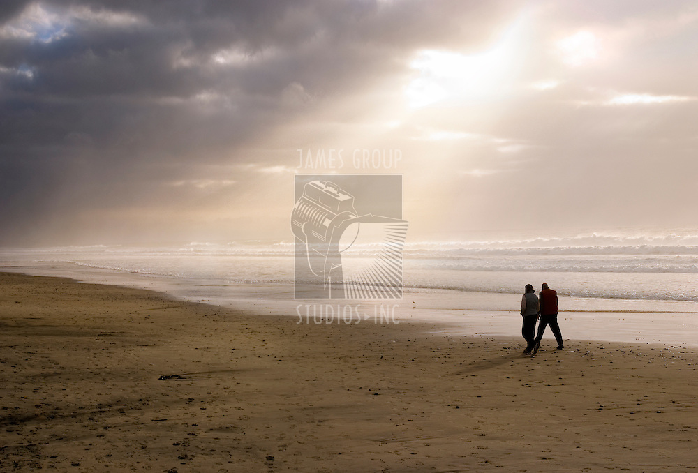 A couple walking on the beach with powerful sunburst beaming through the clouds.
