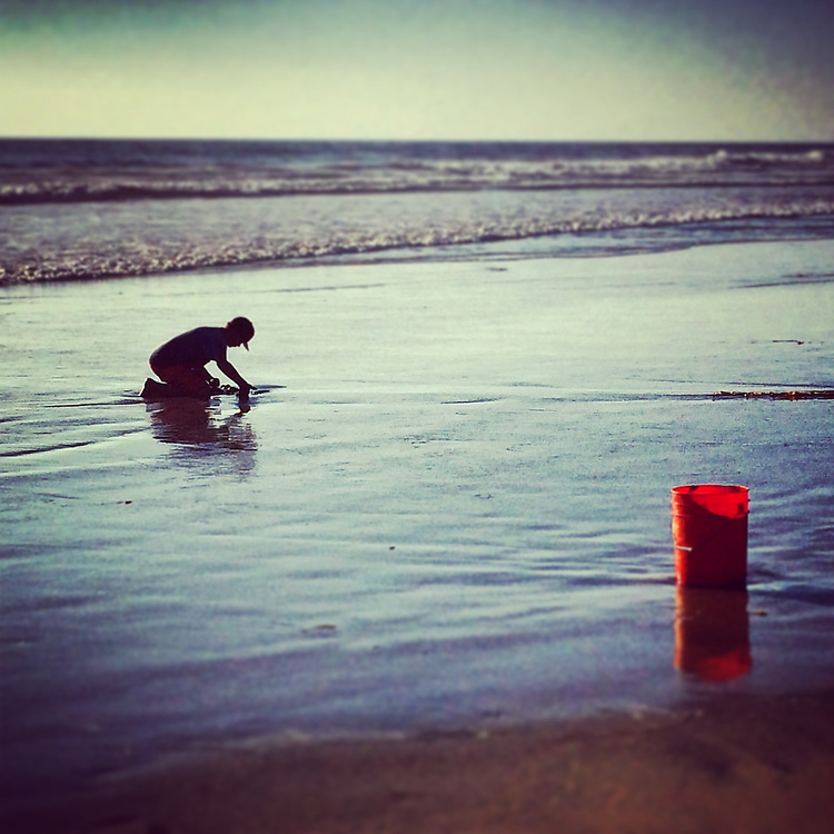 Boy with red bucket digging for bait to go fishing at the beach in Del Mar,CA