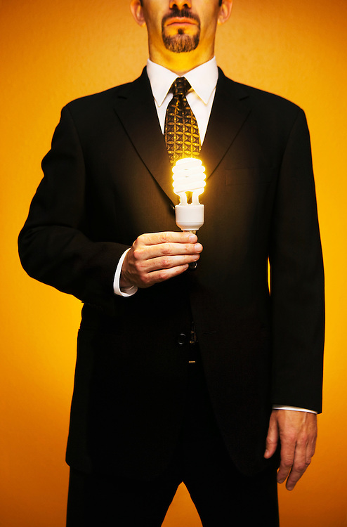 Caucasian businessman in a suit stands holding a lit compact flourescent light bulb in his hand.