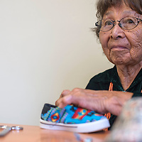 Anna Jones Yazzie, the face of Anna & Family Creations, works on hand sticking a shoe at their office in Gallup Tuesday.