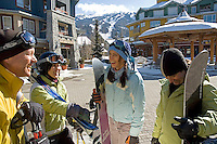 A group of skiers and snowboarders pause for conversation in Whistler Village on a sunny winter day.