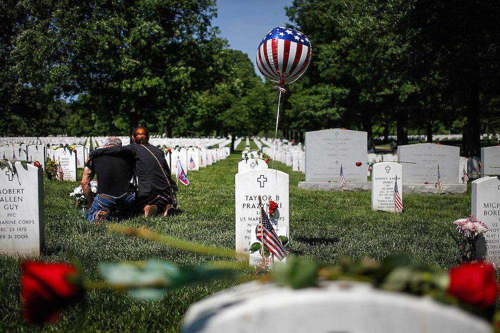 Visitors grieve at a grave in Section 60, where many casualties of the U.S. wars in Iraq and Afghanistan are buried, on Memorial Day at Arlington National Cemetery.