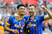 AFC Wimbledon striker Lyle Taylor (33) and AFC Wimbledon defender Jon Meades (12) celebrate promotion in front of the AFC Wimbledon fans after the Sky Bet League 2 play off final match between AFC Wimbledon and Plymouth Argyle at Wembley Stadium, London, England on 30 May 2016. Photo by Graham Hunt.