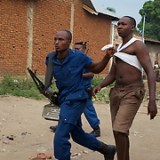 A Burundian National Police officer arrests a local man during a raid in Cibitoke neighbourhood, Bujumbura.