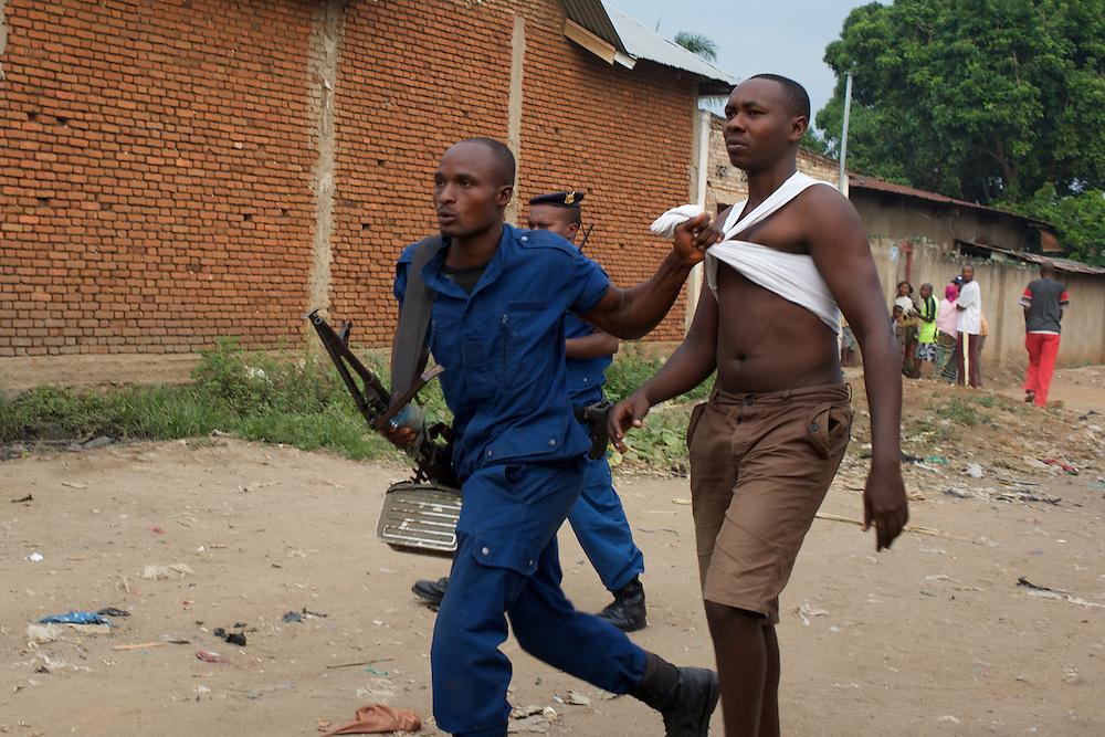 A Burundian National Police officer arrests a local man during a raid in Cibitoke neighbourhood, Bujumbura.
