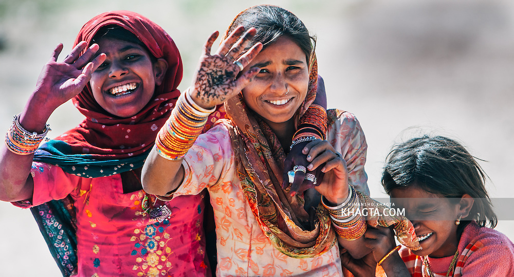 Portrait of ethnic Rajasthani girls waving and smiling happily at the camera