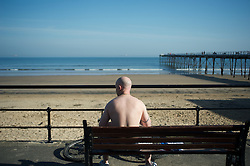 © Licensed to London News Pictures. 28/03/2012..Saltburn, England..A man soaks up the rays as temperatures rise this week at the beach at Saltburn in Cleveland. Attracting many visitors as they enjoy the warm weather...Photo credit : Ian Forsyth/LNP