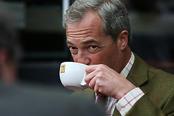 © Licensed to London News Pictures. 25/05/2016. Chapeltown, UK. Nigel Farage sips a cup of tea in Chapeltown, South Yorkshire, during the UKIP Referendum open top bus in tour. The party's purple open top battle bus is touring the country in the run up to the EU referendum. There is just a month to go until the UK's referendum on it's membership of the European Union. Poll stations will open their doors on Thursday 23 June. Photo credit : Ian Hinchliffe/LNP