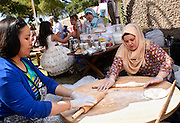 Aichu Zhalilova, (left), and Gulnara Akhmedova make traditional gozleme, a rolled dough folded, filled with cheese or meat, then grilled, at the Turkish booth at Tucson Meet Yourself, an annual festival celebrating culture and diversity in Tucson, Arizona, USA.