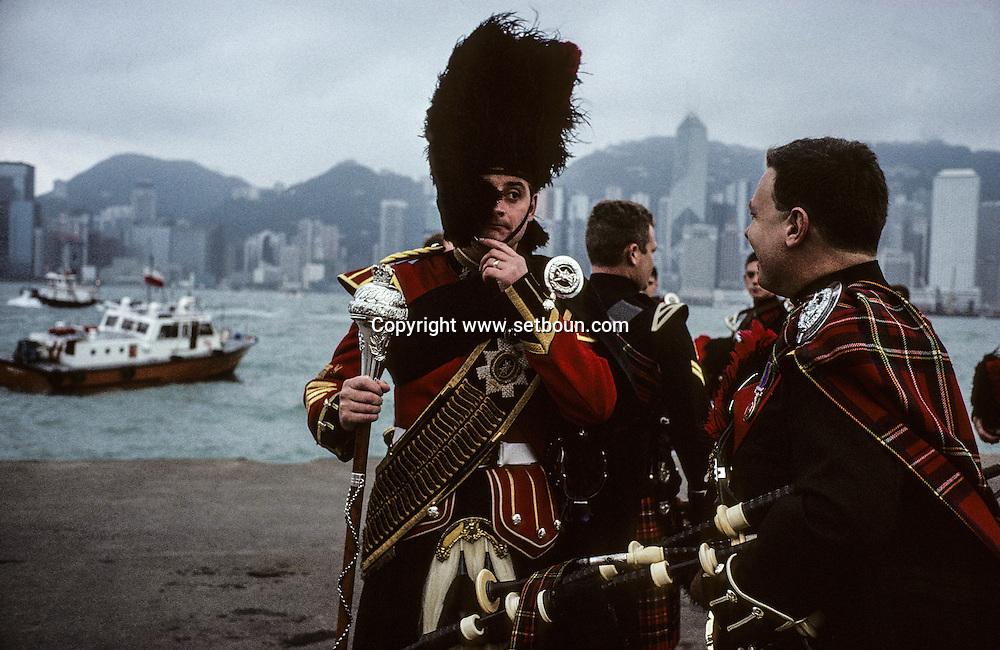 Hong Kong. Black Watch -  royal highland regiment (GB) in front of Victoria island skyline; before their departure to Belfast     / Dernière parade de l'orchestre de cornemuses du bataillon  écossais - Blackwatch -  sur les quais de Kowloon face à l'île Victoria.  / R00057/8    L1781  /  P0000280