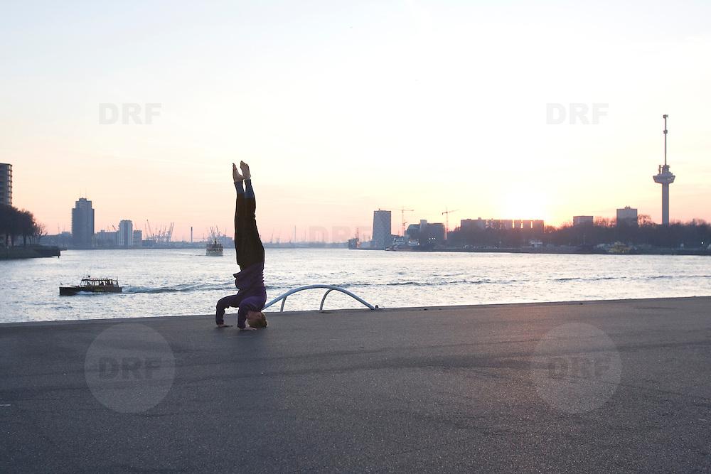 Nederland Rotterdam 21-03-2009 20090321Foto: David Rozing ..Rotterdam kop van zuid, vrouw doet verschillende oefeningen, een mix van joga, dans, capoeira, martial fighting art en meditatie. Handstand, op je kop staan. Woman doing physical exercise in open air in city of Rotterdam   Foto: David Rozing