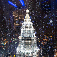 Asia, Malaysia, Kuala Lumpur, View through rain-covered window of 86th Floor Observation Deck of Petronas Towers on stormy evening
