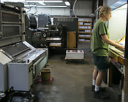 Norman Phillips of Holley checks a fresh print at Conolly Printing in Gates on Wednesday, June 17, 2015.
