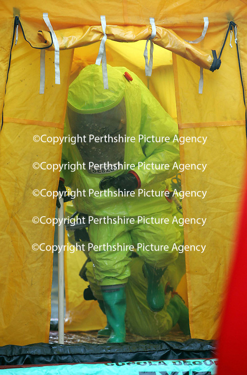 Firefighters in chemical protection suits wash themselves down after dealing with an ammonia leak at the Drumhar Health Centre in Perth.  The leak/spill was caused by and old fridge.<br /><br />Picture by Graeme Hart.<br />Copyright Perthshire Picture Agency<br />Tel: 01738 623350  Mobile: 07990 594431