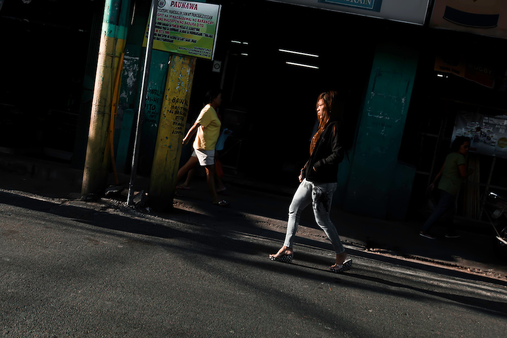 Woman walks street in late afternoon, in Manila, Philippines. Copyright 2015 Reid McNally.