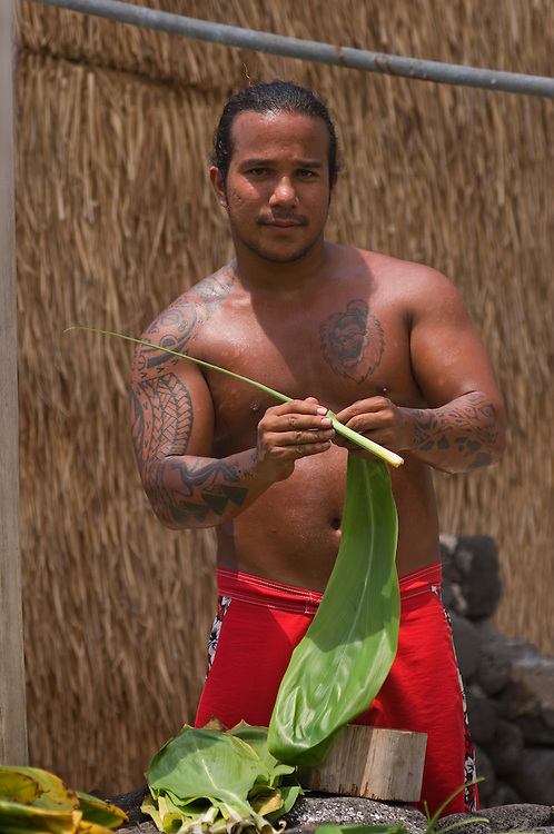 Young Hawaiian man stripping ti leaves for community cultural project at Ahu'ena Heiau, Kailua-Kona, Island of Hawaii.