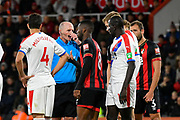 Referee Mike Dean has words with Mamadou Sakho (12) of Crystal Palace before the free kick was taken when he elbowed Jefferson Lerma (8) of AFC Bournemouth during the Premier League match between Bournemouth and Crystal Palace at the Vitality Stadium, Bournemouth, England on 1 October 2018.