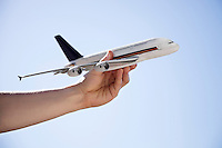 Close-up of hand flying toy airplane against clear sky