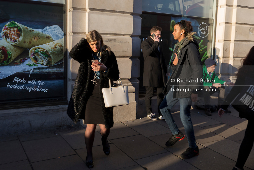 A lady uses her phone outside the branch of M&S Food, on Piccadilly, on 20th January 2020, in London, England.