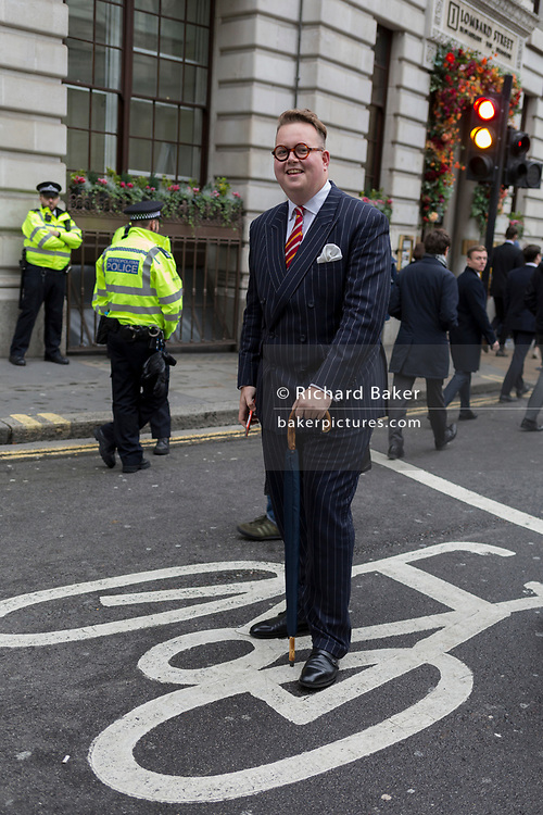 A businessman in a pinstripe suit walks through environmental activists protesting about Climate Change during the blockade outside the Bank of England in the heart of the capital's financial district, the City of London aka the Square Mile, on the seventh day of a two-week prolonged worldwide protest by members of Extinction Rebellion, on 14th October 2019, in London, England.