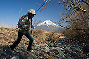 With Mt Fuji in the background, a young trekker skips across a dried up stream on a walk that takes trekkers through parts of the Asagiri Plateau in Shizuoka Prefecture Japan on 22 March 2013.  Photographer: Robert Gilhooly