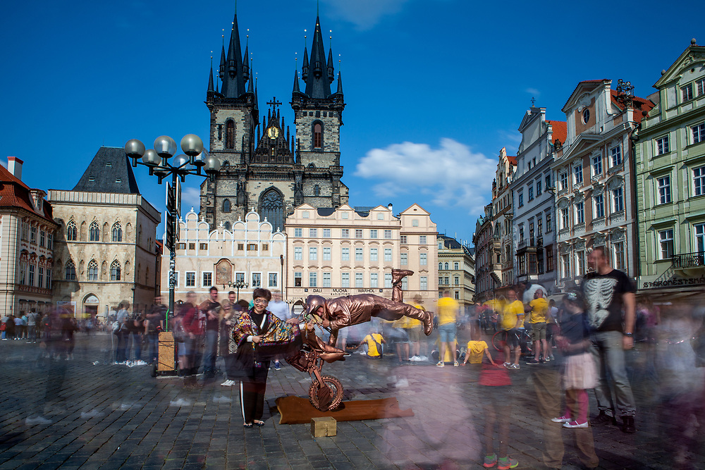 """A tourist is getting a photograph with  a street perfomer on a motorcycle in-front of a crowd at Old Town Square. The """"Church of Our Lady before Týn"""" in the back."""