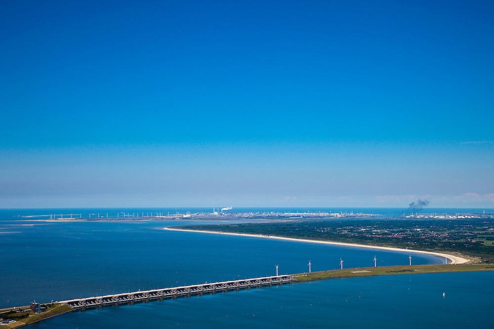Nederland, Zuid-Holland, Haringvliet, 12-06-2009; Haringvlietsluizen en Haringvlietdam, gezien naar Rockanje op het eiland Voorne-Putten, onder in beeld de damaanzet op Goeree-Overflakkee. Op het tweede plan aanleg tweede Maasvlakte, Maasvlakte (met E ON centrale) en olieraffinaderijen in Europoort (vlnr). De sluizen, onderdeel van de Deltawerken, zijn spuisluizen en zorgen er voor dat het zoete water uit het Haringvliet (rechts op de foto) zoals aangevoerd door Maas en Rijn geloosd kan worden. In het kader van modern natuurbeheer  ('getemd getij') gaan de sluizen tegenwoordig bij eb én vloed beperkt open, om de getijden hun enigszin terug te laten komen in achterliggende estuarium .Dam and sluices between islands Voorne-Putten en Goeree-Overflakkee (bottom); the sluices are for draining water coming from the rivers Rhine and Maas (Meuse) from the natural bassin (right) to the North sea (left). Modern ecolical insight has led to opening the sluices semi-permanently, resulting in the estuary function of the Haringvliet patially being restored.Swart collectie, luchtfoto (25 procent toeslag); Swart Collection, aerial photo (additional fee required).foto Siebe Swart / photo Siebe Swart