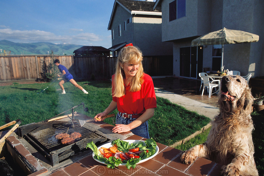 Stephen Webb mows the lawn with a push mower while his wife Kathryn Webb grills hamburgers in the backyard of their new Fremont, California home in a subdivision as their dog looks on. MODEL RELEASED. USA.