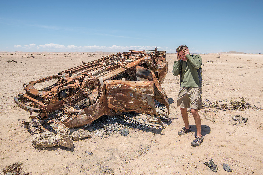 A tourist holding a silly pose while being photographed next to the frame of an abandoned, rusted car in the Namib desert, located in Namibia, Africa.