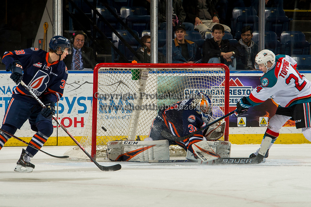 KELOWNA, CANADA - FEBRUARY 23: Kyle Topping #24 of the Kelowna Rockets takes a shot on Dylan Ferguson #31 of the Kamloops Blazers on February 23, 2019 at Prospera Place in Kelowna, British Columbia, Canada.  (Photo by Marissa Baecker/Shoot the Breeze)