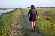 Woman walking along coast path Alderton and Bawdsey, Suffolk, England