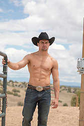 Shirtless cowboy on a ranch opening a gate