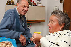 Wheelchair user with Spina Bifida with her father drinking tea.