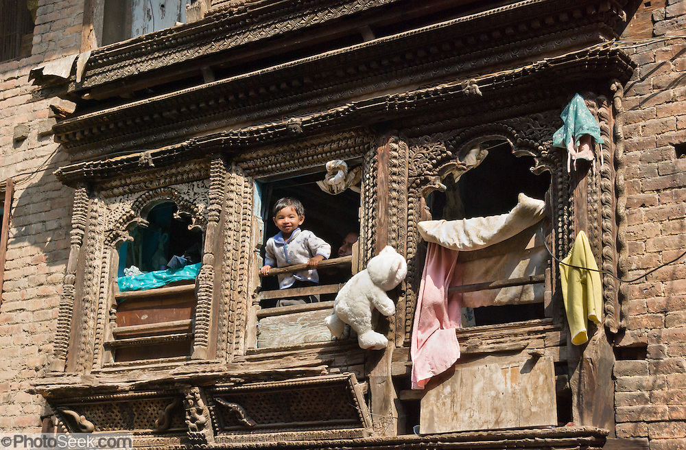 Near Durbar Square, Kathmandu, a child looks out his home window, which is framed with ancient carved wood, with a modern Teddy bear attached. The Newar rulers of the Malla Dynasty controlled the Kathmandu Valley and nearby areas from the 12th to 17th centuries, a period rich in wood and brick architecture that remains today. Kathmandu, the largest city in Nepal (700,000 people) stands at an elevation of 6235 feet / 2230 meters.