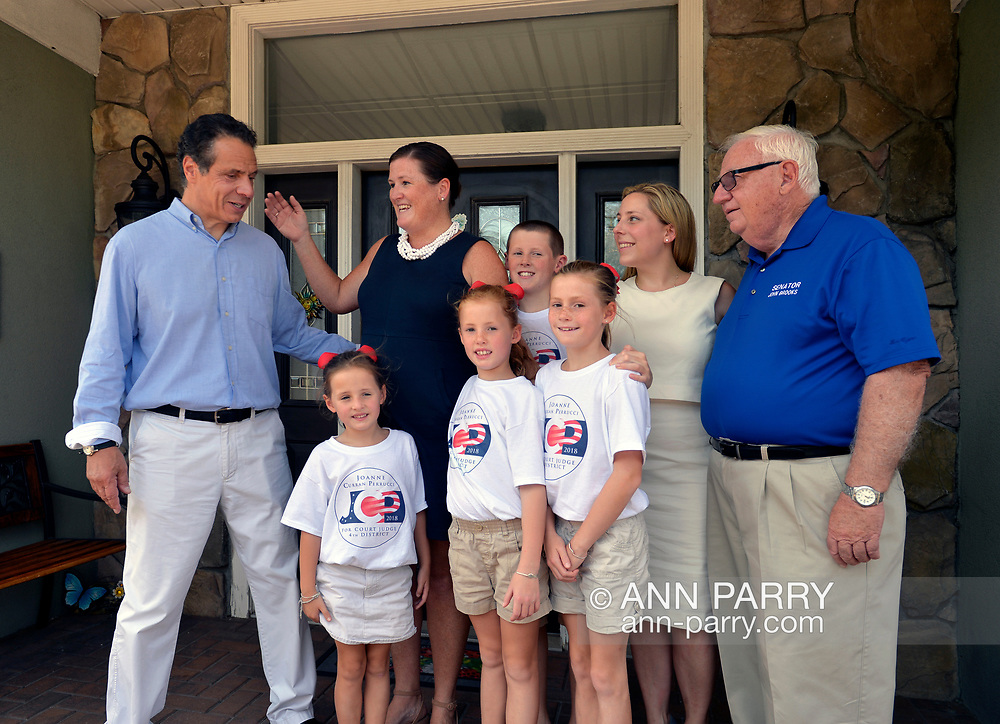 Massapequa, New York, USA. August 5, 2018. L-R, Governor ANDREW CUOMO; JOANNE CURRAN PERRUCCI, candidate for Court Judge 4th District; Perrucci's four young children, three daughters and a son; LIUBA GRECHEN SHIRLEY, Congressional candidate for NY 2nd District; and NY Senator JOHN BROOKS (D-Seaford), gather as Cuomo's about to leave after joint campaign office opening for Grechen Shirley and Sen. Brooks, aiming for a Democratic Blue Wave in November midterm elections.