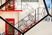 Miami Modern stair railings and a man making a phone call at a small, Miami Beach apartment building.