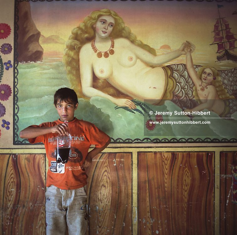 A young Roma boy stands beside a mermaid painted on the wall of a Roma home, in the old part of the Sintesti Roma camp. Mermaids are very popular as wall decoration, but no-one within the camp knows the reason why they were first painted.