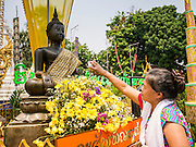 07 APRIL 2013 - CHIANG MAI, CHIANG MAI, THAILAND:  A woman pours water over a statue of the Buddha to make merit at Wat Chang Yuen in Chiang Mai, Thailand. The temple was one of the few temples maintained by the Burmese during their 200 year occupation of Chiang Mai. Chiang Mai is the largest town in northern Thailand and is popular with tourists and backpackers.   PHOTO BY JACK KURTZ