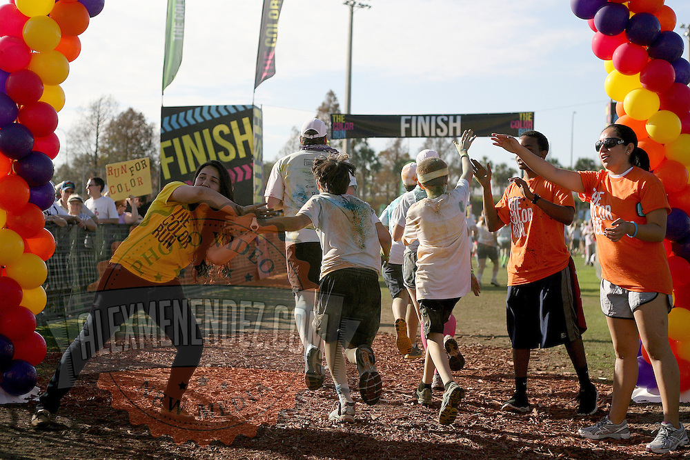 "Participants of the Color Run Orlando event react to getting covered by the colored dust as they attempt to finish the 5K.  Billed as the ""Happiest 5K on the Planet,? the Color Run is a family-friendly run for those who don't mind getting dust thrown at them after beginning the race with a plain white t-shirt on. This is the first event of the season and occured at the Citrus Bowl in downtown Orlando, Florida on January 13, 2013. (AP Photo/Alex Menendez)"