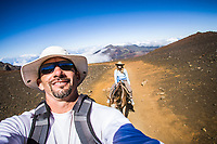 A man on a horse taking a selfie of him and his wife, Haleakala Crater, Haleakala National Park, Maui, Hawaii.