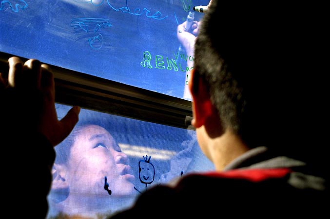 Fremont, CA. - 2/20/03 - Raymond Jiang, age 9, draws on the window as part of an assignment in his art class at Warm Springs Elementary School in Fremont.
