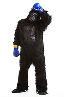Tired young man in gorilla costume and boxing gloves against white background