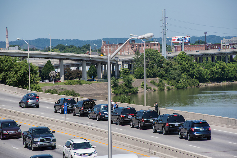 Photojournalists riding in an SUV ahead of the hearse in the June 10, 2016 Muhammad Ali funeral procession on Interstate 64 jump out for pictures during a pause in front of the Muhammad Ali Center before exiting downtown at 9th Street. (Photo by Brian Bohannon)