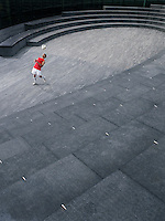 Man bouncing soccer ball off chest in the Scoop amphitheatre London England elevated view