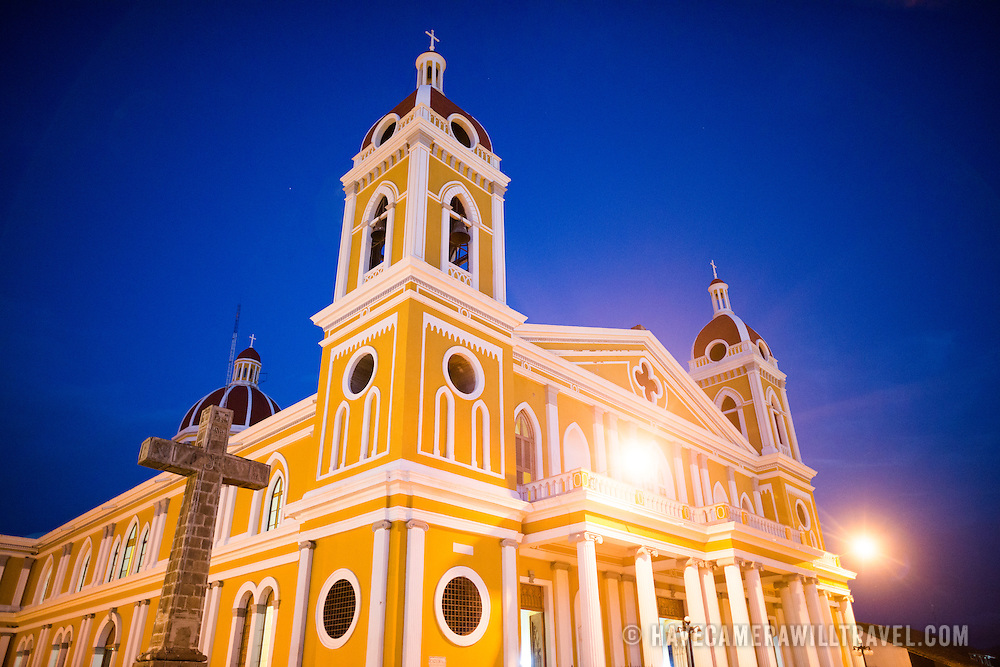 "There has been a church on this spot since about 1525, but it was destroyed and rebuilt several times in the following centuries as the city of Granada was attacked by pirates and others. Construction on the current version began in 1888 but was not fully completed until 1972. With its distinctive yellow with white trim exterior, it stands over Parque Central in the heart of Granada, Nicaragua. The cross was installed in 1901 and is made of basalt. At the top the inscription INRI is read, and a chalice and a bunch of grapes symbolizing the blood of Christ . In the center, where the arms are crossed, the X and P interlaced letters: monogrammed initials Redeemer. On the left arm, there are four quadrangles, with a cross in the center of each- symbolizing the four Gospels . On the right arm, two arms entwined, symbol of the union of Christ with humanity. At the foot of the cross, there is a skull on two femurs crossed to represent the bones of Adam , finally-in the base-, bears the inscription ""Jesus Christ God, man lives, reigns and rules""."