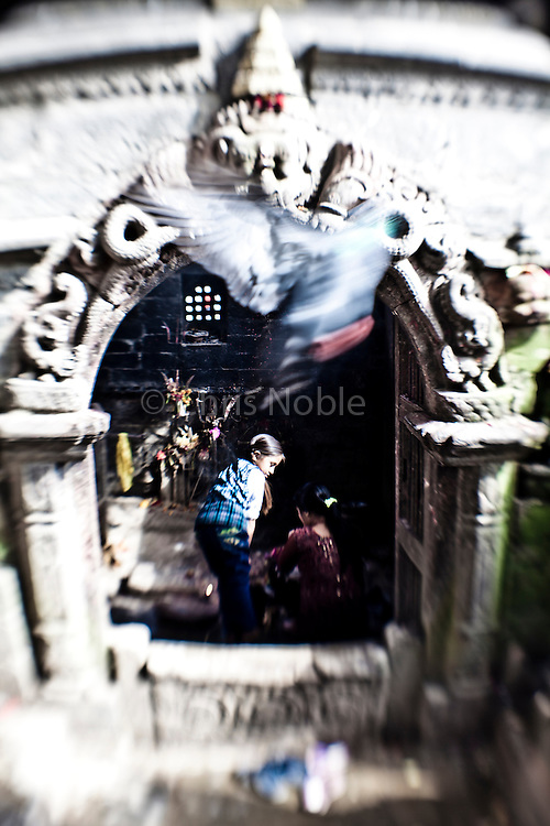 A mother and daughter tend a shrine in Bhaktapur's Durbar Square.