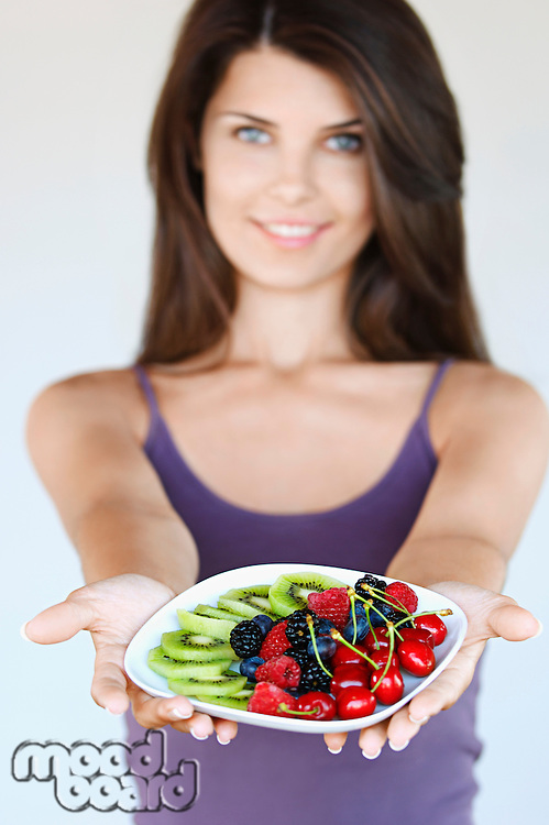 Young woman holding plate of fruit focus on foreground
