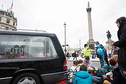 London, UK. 8 October, 2019. Climate activists from Extinction Rebellion sit around a hearse containing a coffin used to block access from Whitehall to Trafalgar Square the previous day during International Rebellion protests to demand a government declaration of a climate and ecological emergency, a commitment to halting biodiversity loss and net zero carbon emissions by 2025 and for the government to create and be led by the decisions of a Citizens' Assembly on climate and ecological justice.