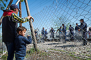 A father and son stand in front of a fence guarded by Greek police at the Greece Macedonia border.