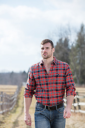 rugged masculine man in a flannel shirt on a ranch
